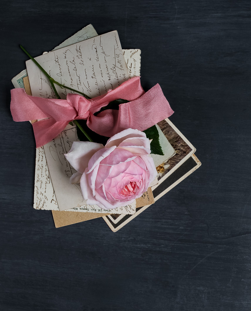 Rose ribbon around old letters and rose